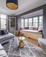 Lichtdurchflutetes Wohnzimmer in Grautönen mit Sprossenfenstern