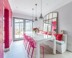 Hot-pink chairs and wall in bright dining room with large mirror