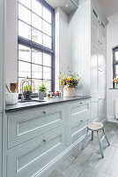 Window in country-house kitchen with pale grey panelled cabinets