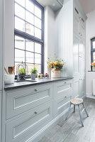 Fenster in der Landhausküche mit hellgrauen Kassettenfronten