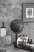 Gewürze, Essig und Öhl auf Tablett, schwarzer Globus und schwarz-weiße Vase auf Ablage