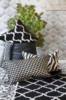 Schwarz-weißer Teppich und Kissen vor Blätterzweig