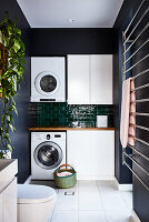 Washing machine and tumble dryer against tiled wall in utility room