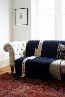 Dark blue quilt on pale button-tufted sofa