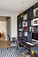 Grey fitted shelving with integrated desks and office chairs