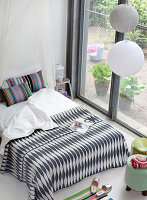 Black-and-white patterned bedspread and brightly striped pillows on double bed next to terrace doors