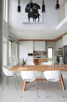 Designer shell chairs around wooden dining table in elegant, double-height dining area