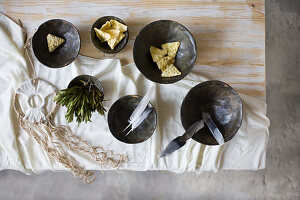 Snacks, feathers and herbs in black bowls and dreamcatcher