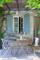 Table and metal chairs on wooden terrace below pergola outside window with blue shutters