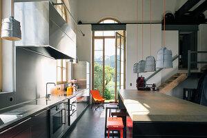 Küchenzeile und Kücheninsel mit Barhockern vor geöffneter Fenstertür in umgebautem Loft