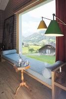 Elegantes Wohnzimmer mit gepolsterter Sitzbank vor Panoramafenster mit Landschaftsblick