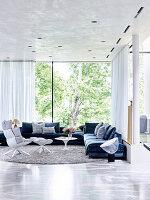 Elegante Lounge mit Polstergarnitur und Designersessel vor Fensterfront
