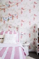 Bett mit weiß-rosa gestreifter Bettwäsche und Tapete mit Vogelmotiv im Mädchenzimmer