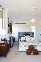 Doppelbett mit blau lackiertem Regal am Kopfende vor Einbauschrank, Koffer am Bettfussende
