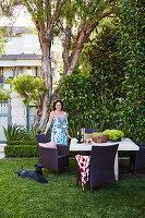 Frau und Hund am Tisch mit Flechtstühlen im Garten unter Baum