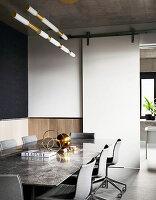 Tisch mit Marmorplatte und Stühle im Besprechungsraum mit Schiebetür