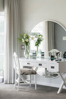 White dressing table against large, round mirror on wall