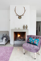 Scatter cushion on antique easy chair with lilac upholstery next to fireplace below antlers on wall