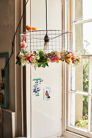 Wire lampshade decorated with garland of fabric flowers and bird figurines