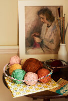 Balls of wool in wire basket, knitting needles and picture of knitting woman