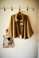 Cape with floral brooch hung from coat rack