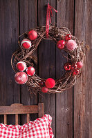 Festive wreath of willow and red baubles hung on wall