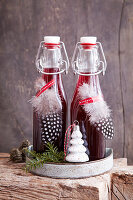 Mulled wine syrup in swing-top bottles decorated with feathers