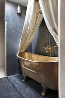 Free-standing copper bathtub with canopy and curtains in niche