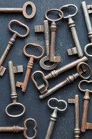 Alte rostige Schlüssel auf schwarzem Grund mit abgeblätterter Farbe