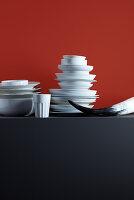 Gestapeltes Geschirr, ein Becher und ein Horn vor rotem Hintergrund