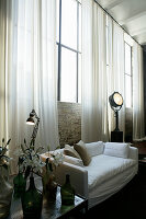 White sofa against brick wall with industrial windows and long curtains