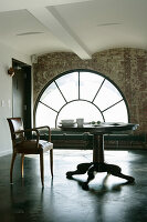 Old leather chair at pedestal table in front of large arched window