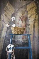 Korb mit Baumwollknospen auf einer blauen Leiter mit Traumfänger