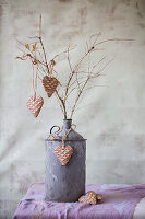 Heart-shaped pendants with waffle structure on branches in old metal can