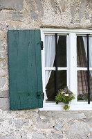 Wildblumenstrauss am Fenster einer Almhütte
