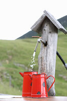 Water running from wooden pump into red enamel jugs