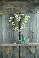 Wreath of cherry blossom and hand-painted green Easter egg on shelf on rustic wooden wall
