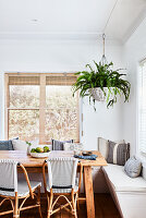 Fern in hanging basket above dining table and corner bench