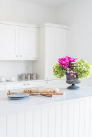 Bread and flower arrangement in bright country-house kitchen