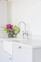 Flower arrangement next to sink in bright country-house kitchen