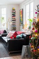 Christmas tree, black leather sofa, standard lamp and bookshelves in living room