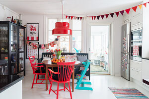 Red Christmas decorations, dining table and chairs and display case in white kitchen-dining room