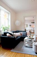 Dark sofa in living room with open doorway leading into dining room