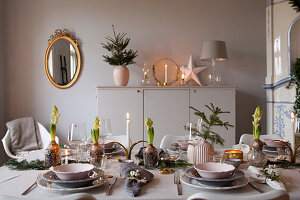 Row of hyacinths on dining table festively set in shades of grey