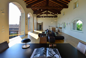 View across table to leather sofa set in elegant loggia with arches in renovated farmhouse