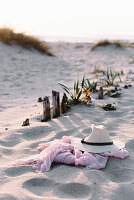 Straw hat and pink scarf lying on sand of beach on sunny day