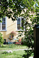 Garden table and chairs outside house in sunny garden
