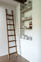 Wooden ladder against white wall next to shelves of crockery