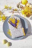 Frühlingsblüten in gefalteter Serviettentasche als österliche Tischdeko