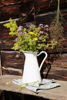 Bunch of wildflowers in white enamel jug